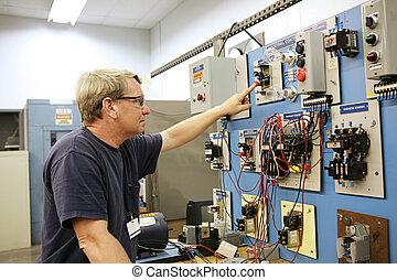 Motor Control Center - An electrical teacher working on an...