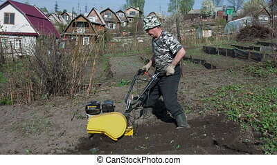 Motor cultivator - The gardener processes the earth a...