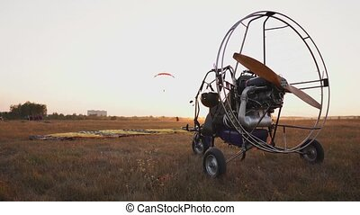 Motor paraglider stands at the airport in the rays of sunset...