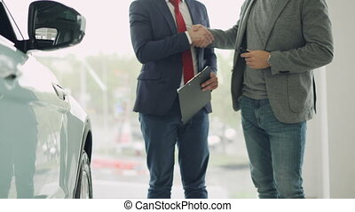 Motor showroom employee is giving car key to young male buyer and shaking hands, dealer is holding documents and gesturing. Selling and buying transport concept.
