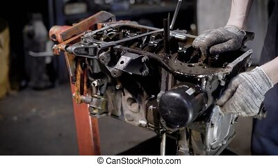 motor technician is disassembling old dirty car engine,...