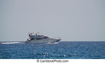 Motor yacht with people sailing on the waves. Slow motion -...