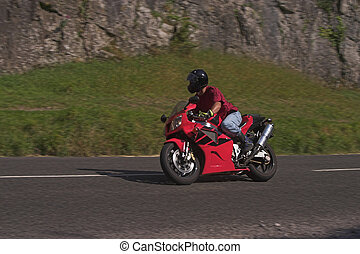 Motorbike climbing a hill at speed, with background showing...