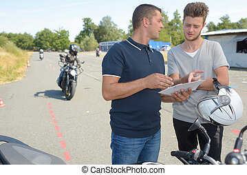 motorbike instructor showing a paper to the student