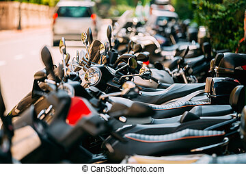 Motorbike, motorcycle scooters parked in row in city street