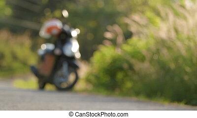 Motorbike parked on the road near bushes. Sunset light...