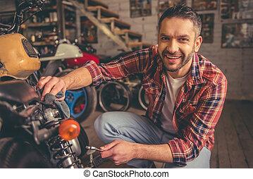 Motorbike repair shop - Handsome man is looking at camera...