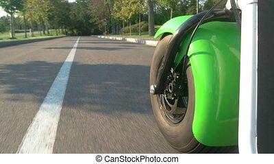 Motorbike wheel on road background. Asphalt and green trees....