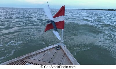Motorboat in the sea with waving flags