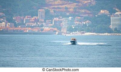 Motorboat moving at sea against Mediterranean resort scenery...