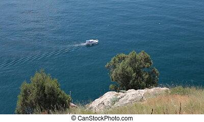 motorboat sailing along seashore