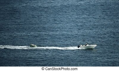 Motorboat towing inflatable recreational raft at sea, slow...