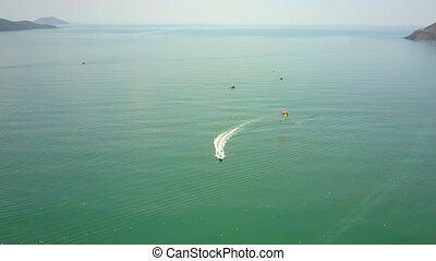 motorboat with foamy trace pulls parachute on ocean - Aerial...