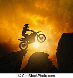 Active sports background - motorcircle rider silhouette, dramatic dark sunset in rocks