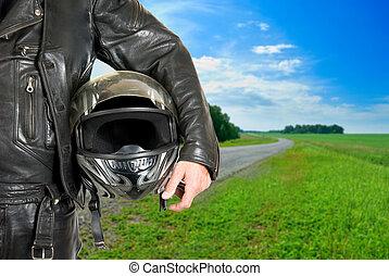 biker - motorcycle biker with helmet closeup on a road