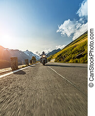 Motorcycle driver riding in Alpine highway. Outdoor photography