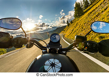 Motorcycle driver riding in Alpine highway, handlebars view,...