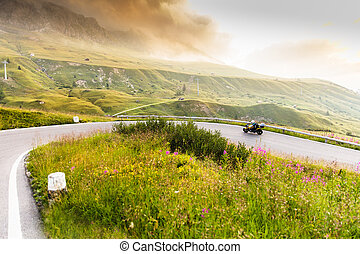 Motorcycle driver riding in Dolomite pass, Italy, Europe.