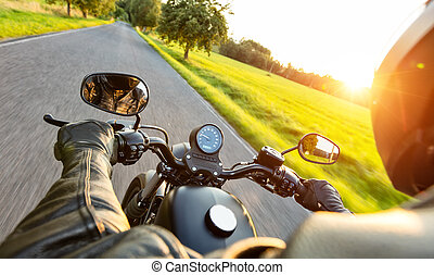Motorcycle driver riding on motorway in beautiful sunset ...