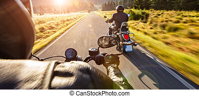 Motorcycle drivers riding on motorway in beautiful sunset...