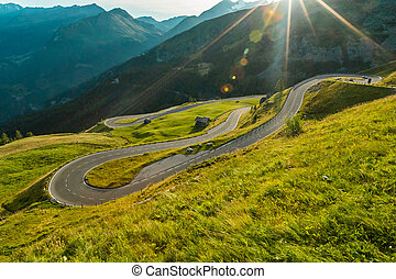 Motorcycle rider driving in Alps, beautiful nature with clear sky.
