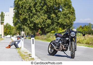 Motorcycle rider sitting near custom made scrambler style cafe racer