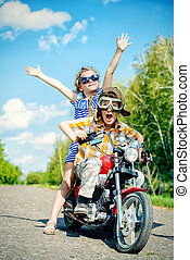 motorcycle - Happy kids go on a journey on a motorcycle on a...