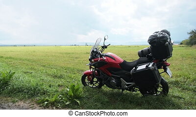 Motorcycle travel. Tourist motorcycle with trunks against a landscape of mountains and fields.