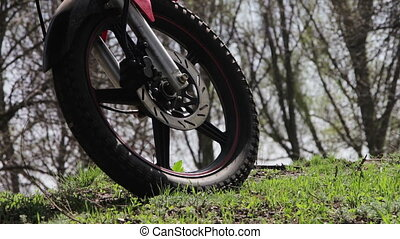 Motorcycle Wheel Near the Highway on Which Passing Cars