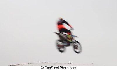 Motorcycles in flight over head, high jump, motocross winter