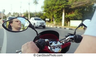 Motorcyclist drives motorcycle on asphalt road while...