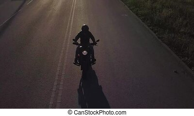 Motorcyclist driving his motorbike on the road during sunset during sunset