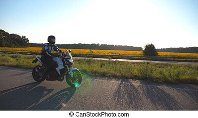 Motorcyclist driving his motorcycle on the country road with sunflower field at background. Young man in helmet riding on a moto bike at sunset. Slow motion Close up