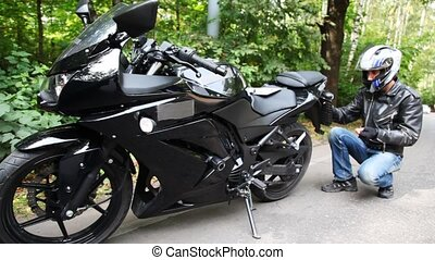 Motorcyclist fastens licence plate on black motorcycle