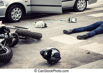Motorcyclist helmet and motorbike on the street after collision with a car