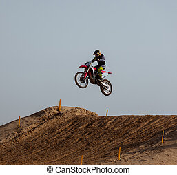 Motorcyclist jumping with his motorcycle in the air captured doing stunt in motocross race.