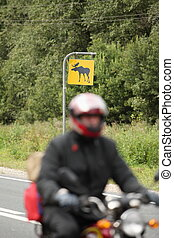 motorcyclist on a background road sign