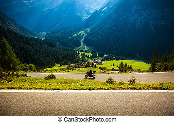 Motorcyclist on mountainous highway - Motorcyclist riding on...