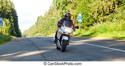 motorcyclist goes on the road to a sports motorcycle
