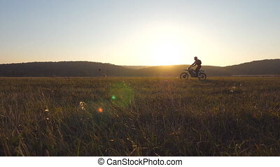 Motorcyclist passing through large field with beautiful...