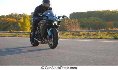 Motorcyclist racing his motorcycle on autumn country road. Young man in helmet riding fast on modern sport motorbike at highway. Guy driving bike during trip. Concept of freedom and adventure