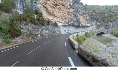 Motorcyclist Rides on a Beautiful Landscape Mountain Road in...