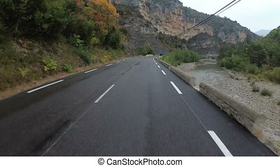 Motorcyclist Rides on a Beautiful Landscape Mountain Road in France. Rainy weather. First person view