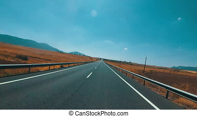 Motorcyclist Rides on a Landscape Desert scenic and empty road in Spain. First person view