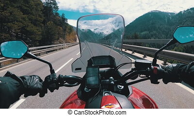 Motorcyclist Rides on Beautiful Landscape Mountain Road near Snowy Switzerland Alps