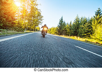 Motorcyclist riding  chopper on a road
