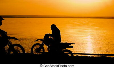 Motorcyclist silhouette at sunset. He freely travels around...