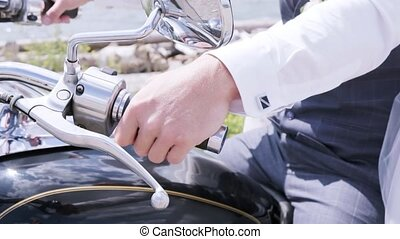 Motorcyclist sitting on his motorcycle , hand close up