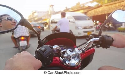 Motorcyclist wearing sunglasses drives motorcycle while...