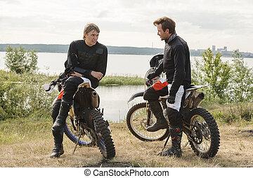Motorcyclists chatting near lake